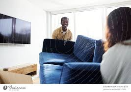 junges paar im neuen zuhause trägt sofa im wohnzimmer am