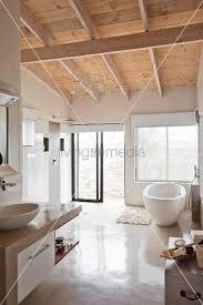 weisses modernes bad mit holzdecke und freistehender wanne