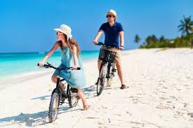 Father And Her Little Daughter Riding Bikes At Tropical Beach Having Fun Together Stock Photo