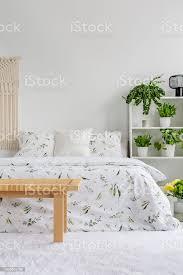 weiße schlafzimmer interieur mit frischen pflanzen auf gestell legen blumen blätter auf doppelbett teppich auf dem boden und leer für ihr poster an