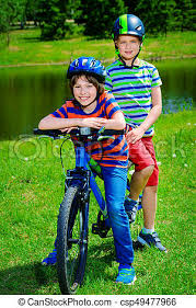 Active Friends Outdoor Happy Boys Are Riding Bikes In The Park
