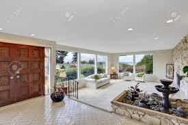helles wohnzimmer mit brunnen in luxus haus ansicht der eingangshalle mit fliesenboden und holztür
