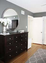 Benjamin Moore Amherst Gray In This Bedroom With A And White Patterned Rug Trim Dark Wood Furniture Round Mirror Wall Color Grey B
