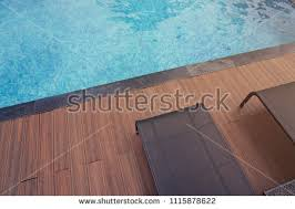 Top View Of Swimming Pool With Relax Black Modern Rattan Chairs On Wooden Floor 1115878622