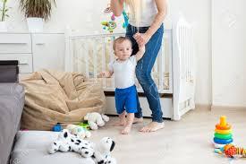 junge mutter die baby durch hände hält und am wohnzimmer geht