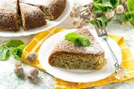 köstlicher selbst gemachter mohnkuchen backen im multikocher ganzer kuchen und stück auf gelber servietten minzen und trockener mohnkapsel mit