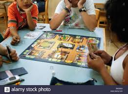 Four Teens Playing Cluedo A Murder And Strategy Board Game