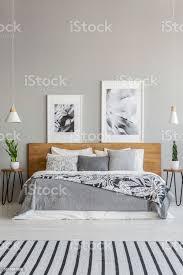 poster auf hölzernen kopfteil des bettes mit gemusterten decke innen grau schlafzimmer mit teppich echtes foto stockfoto und mehr bilder bett