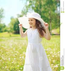 little child wearing a straw hat and white dress in summer