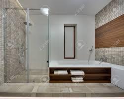 badezimmer in einem modernen stil mit hellen fliesen an der rückwand die seitenwände ist mit braun beige mosaik und einer holzplatte dekoriert auf