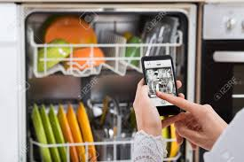 Close Up Of Person Hands Operating Dishwasher From Mobile Phone Stock Photo