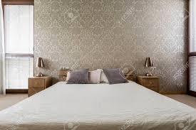 helles schlafzimmer mit dekorativer tapete und großem doppelbett
