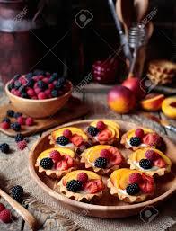 sommernachtisch mit verschiedenen früchten frisches beeren törtchen oder kuchen mit vanillepudding himbeere pfirsich und brombeere für die ganze