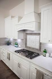 Usa Tile And Marble by A Kitchen Hood With White Wainscoting Trim Stands Over A Marble