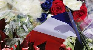 A Bouquet Of Flowers And French Flag Is Seen As People Pay Tribute Near The