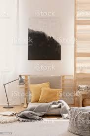 abstrakte malerei an der weißen wand des japanisch inspirierten schlafzimmer design beige futon mit gelben kissen stockfoto und mehr bilder