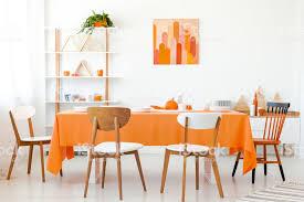 holzstühle an orange tisch in weiß esszimmer interieur mit poster und pflanze echtes foto stockfoto und mehr bilder bunt farbton