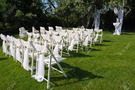 Arch For Wedding Ceremony. White Decorated Chairs On A Green..