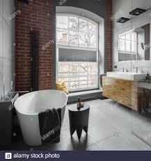 badezimmer im industriestil mit ovaler badewanne und großem