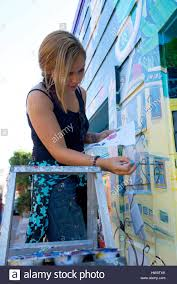 an artist paints a wall mural in balmy alley in the mission