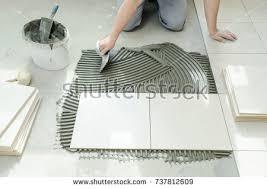 tiler putting tiles adhesive wall notched stock photo 737812609