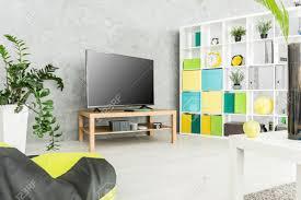 modernes wohnzimmer mit einem fernseher und einem großen regal mit boxen und dekorationsgegenständen