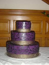 3 Tier Round Wedding Cake Iced In Purple With Gold Ribbon And Black Scrolls