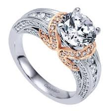 Rose gold is used perfectly in this engagement ring design accenting the gorgeous curves and drawing the eye to the center diamond