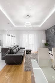 modernes grau weißes wohnzimmer mit puff und abgefallenen decken