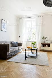 schwarzen tisch auf teppich im hellen wohnzimmer interieur mit grauen unter plakat echtes foto stockfoto und mehr bilder das leben zu hause