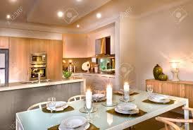 moderne küche und das esszimmer mit weißen kerzen überall weingläser und teller auf dem tisch gibt es hölzerne stühle um den tisch raumdecke hat