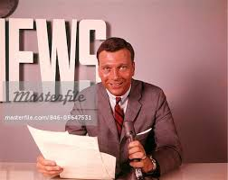 1960s SMILING BROADCAST REPORTER NEWSMAN ANNOUNCER AT NEWS DESK HOLDING MICROPHONE PAPERS READING REPORT