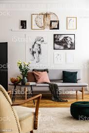 poster über grauen sofa mit kissen im wohnzimmer interieur mit blumen und sessel echtes foto stockfoto und mehr bilder blume