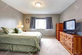 große graue schlafzimmer mit kommode fernseher und blaue vorhänge und grün betten