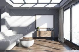 wohnzimmer im loft mit grauen wänden einem sofa einem runden couchtisch und einem großen poster das über einer kommode hängt mock der wiedergabe