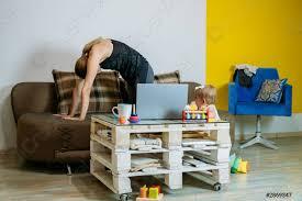 foto auf lager junge frau mutter sitzt mit ihrer kleinen tochter zu hause auf dem sofa und macht übungen beobachtet kurs am