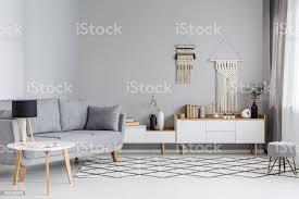 le auf den tisch neben grauen sofa im scandi wohnzimmer interieur mit diy dekor über dem schrank echtes foto stockfoto und mehr bilder
