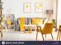 gelbe sessel in weiß wohnzimmer interieur mit poster über
