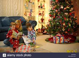 Christmas Tree Books by Mother Reading Books To Children By Christmas Tree Stock Photo