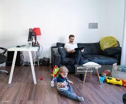 vater arbeitet im wohnzimmer home office mit baby junge