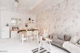 loftstil wohnung großes wohnzimmer mit esstisch und küche zimmer mit weihnachtsbaum bequemes sofa hohe fensterfronten leichte weiße mauer stockfoto