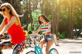 Two Beautiful Tanned Slim Sexy Hipster Girls Engaged In Outdoor Sports Riding Bikes Laughing