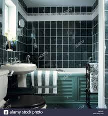 grün weiß handtuch auf badewanne mit louvre verkleidung in