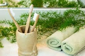 drei biologisch abbaubar kompostierbar bambus zahnbürsten in marmor tasse rolled grüne handtücher in einem spa einstellung grüne pflanze dekor im