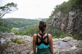 Woman Standing On Cliffs Edge Looking Out At The Rainforest View Below