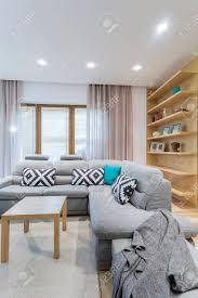 große polster ecksofa mit dekorativen kissen und eine graue decke in einem modernen wohnzimmer