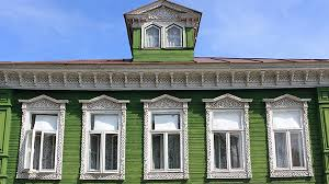 Green House With White Framed And Pointed Windows Mouldings