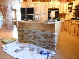 Modish White Kitchen Cabinet Finished With Grey Stone Backsplash
