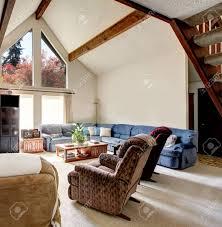 helles großes wohnzimmer mit gewölbter decke und balken teppichboden felswand desing mit komfortablen großen sitzgruppe stühle couchtisch und tv