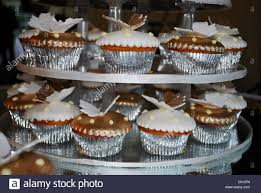 A Plate Of Cup Cakes In Silver Cases With White Icing And Butterfly Decoration On Tiered Cake Stand UK 2008